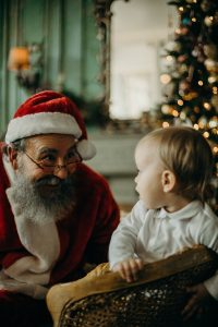 Man In Santa Claus Costume Looking At A Baby 3154249